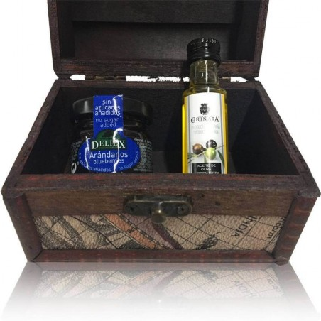 Little chest of dark wood decorated with map with little bottle of olive oil and the marmalade of blueberry