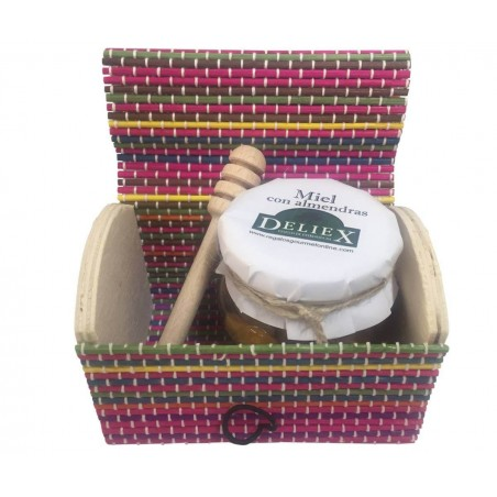 Colorful trunk with jar of honey with almonds and stick taster