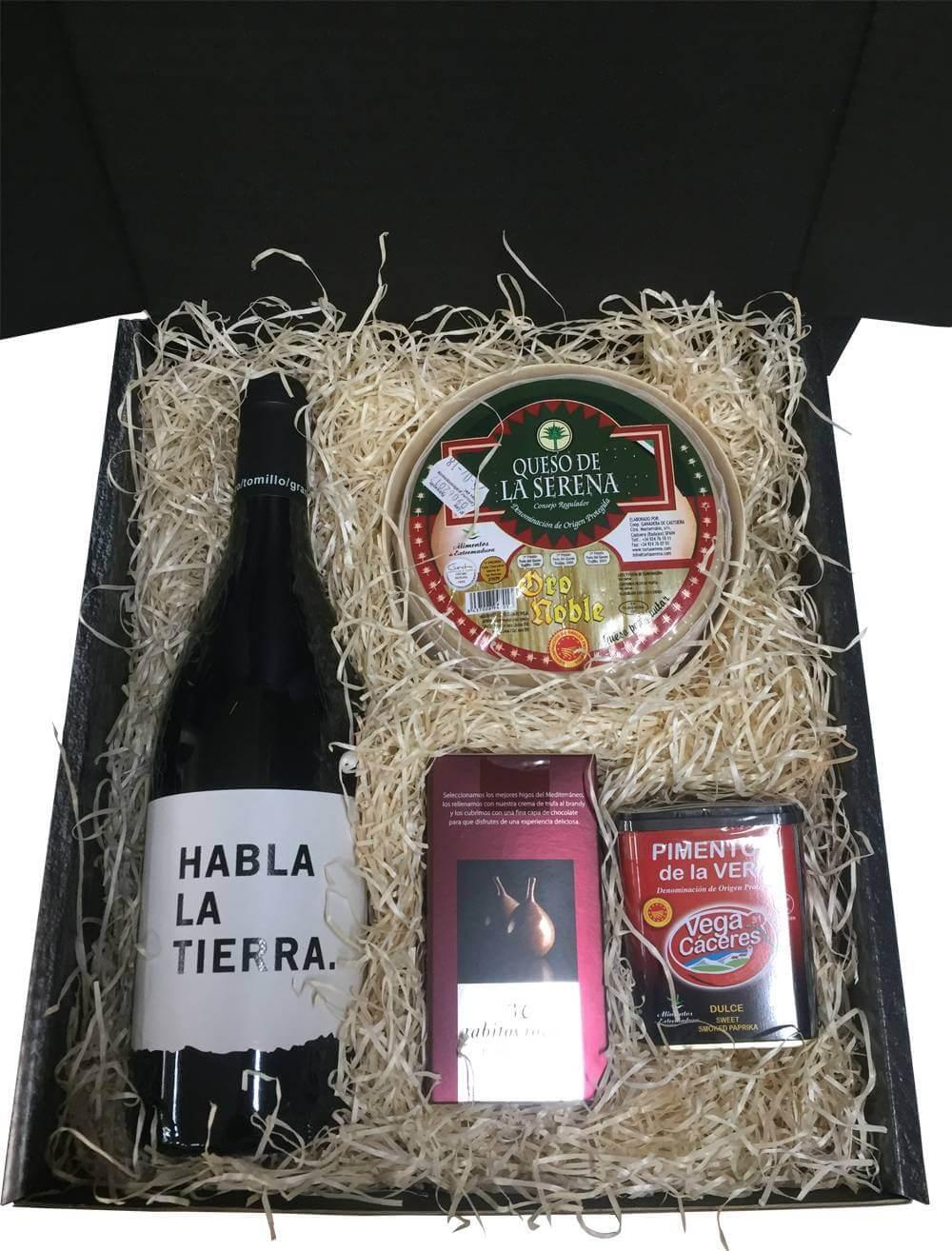 Étui moyen avec du vin, du fromage de gâteau, des chocolats et du paprika pour le cadeau