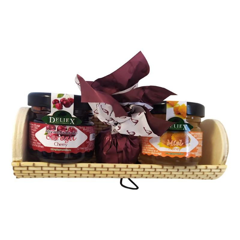 Baúl de mimbre alargado con tarrito de miel, mermelada y bombón